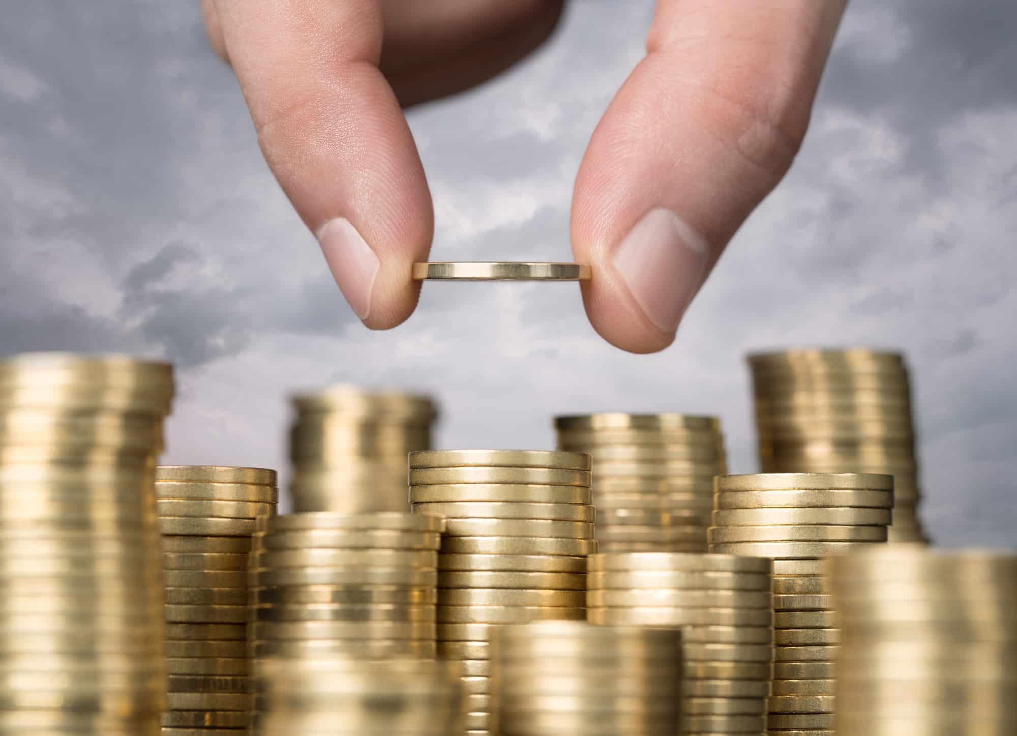 Une main qui pose une pièce qur des colonnes de pièces de monnaie