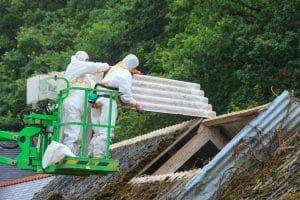 Ouvriers d'une entreprise de démolition en train de retirer des panneaux d'amiante d'une vieille toiture