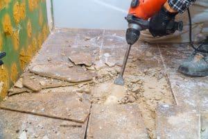 marteau burineur en train de détruire un carrelage lors de travaux de démolition dans une maison