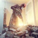 Ouvrier d'une entreprise de démolition en train de détruire une cloison intérieure